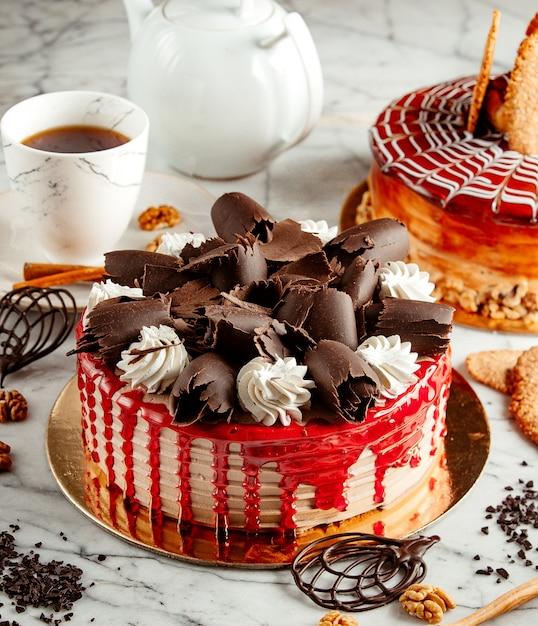 Seitenansicht des obstkuchens mit schokoladenkräuselung und schlagsahne auf dem tisch serviert mit tee Kostenlose Fotos