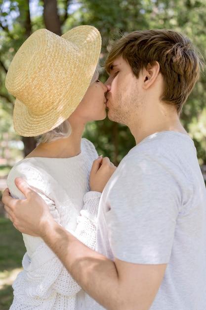 Seitenansicht des paares, das im freien küsst Kostenlose Fotos