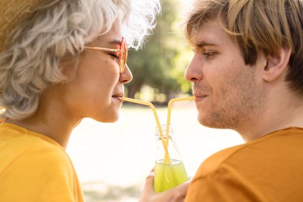 Seitenansicht des paares, das saftflasche teilt, während im park Kostenlose Fotos