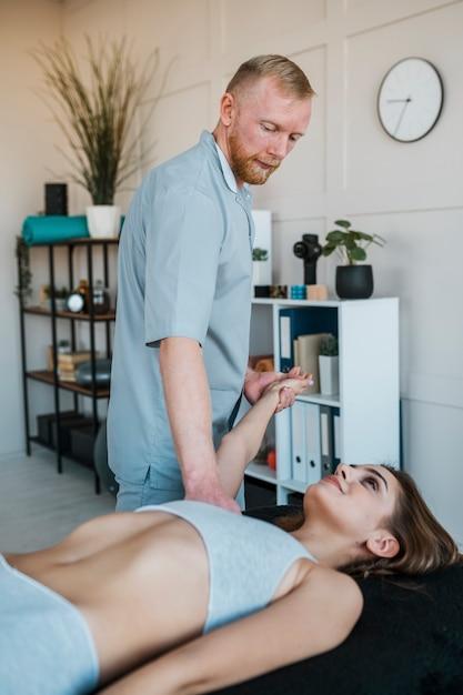 Seitenansicht des physiotherapeuten, der übungen an frau durchführt Premium Fotos