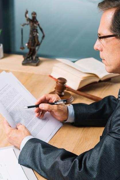 Seitenansicht des reifen männlichen rechtsanwaltlesedokuments im gerichtssaal Kostenlose Fotos