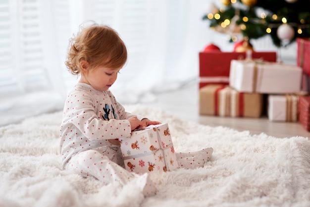 Seitenansicht des reizenden baby, das weihnachtsgeschenk öffnet Kostenlose Fotos