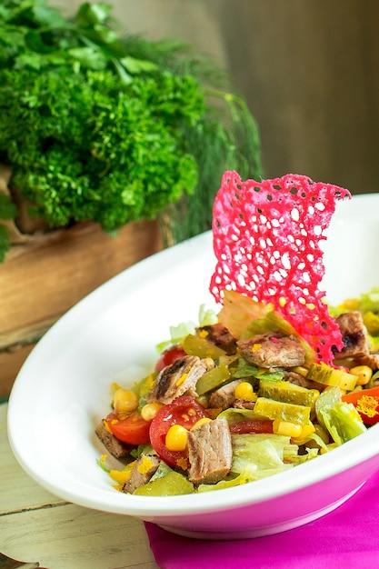 Seitenansicht des rindfleischfleischsalats mit gehacktem gemüse und essiggurken in einer schüssel Kostenlose Fotos