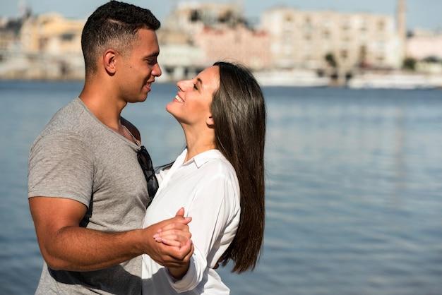 Seitenansicht des romantischen paares, das am strand umarmt Kostenlose Fotos