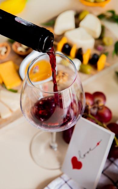 Seitenansicht des rotweins, der in glas und verschiedene arten von käseoliven-walnuss-traube und liebeskarte auf weißem hintergrund fließt Kostenlose Fotos