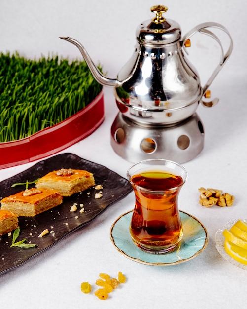 Seitenansicht des schwarzen tees im armudu-glas mit pakhlava Kostenlose Fotos