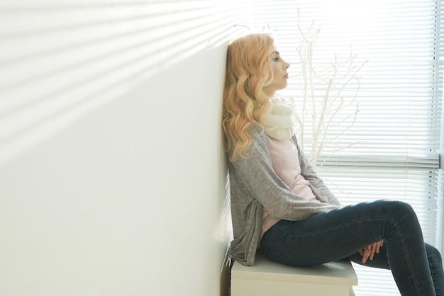 Seitenansicht des sitzens der blonden frau erschöpft und in einem raum erwägend Kostenlose Fotos