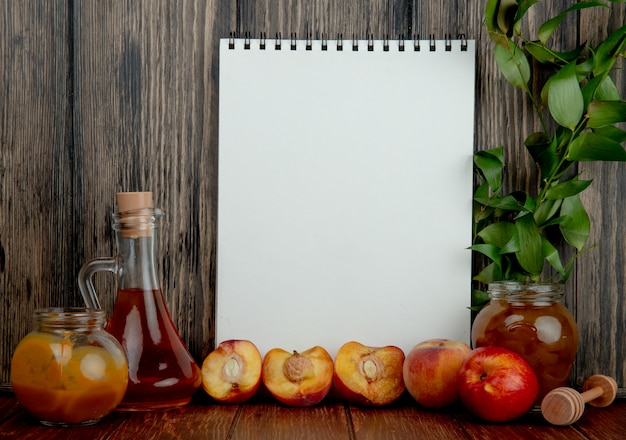 Seitenansicht des skizzenbuchs und einer flasche olivenöl und eines glases mit honighälften frischer süßer nektarinen und eines glases mit pfirsichmarmelade auf rustikalem holz Kostenlose Fotos