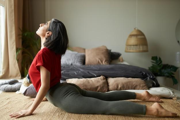 Seitenansicht des sportlichen barfußmädchens mit starkem flexiblem körper, der zu hause trainiert Kostenlose Fotos