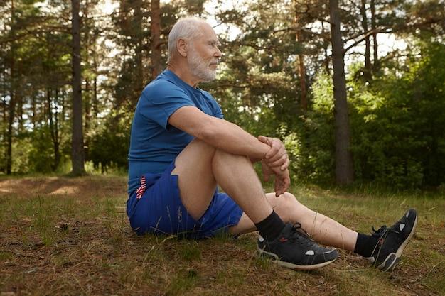 Seitenansicht des stilvollen männlichen rentners mit bart, der schöne landschaft betrachtet, die am waldrand sitzt, sich nach dem morgendlichen cardio-training entspannt, knie mit beiden armen umarmt, friedlichen ruhigen blick hat Kostenlose Fotos