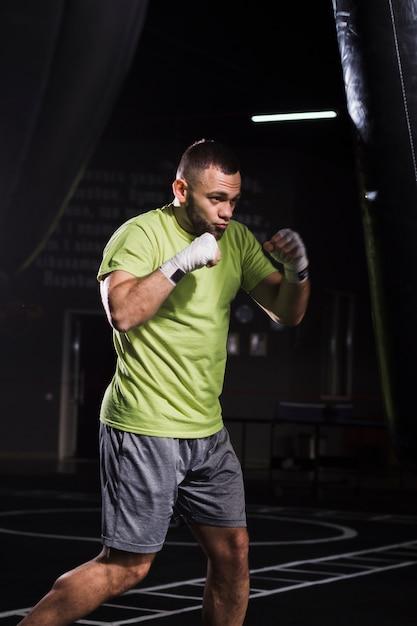 Seitenansicht des tragenden t-shirts und der kurzen hosen des männlichen boxers, die mit sandsack üben Kostenlose Fotos