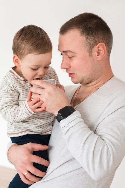 Seitenansicht des vaters, der baby hält Kostenlose Fotos