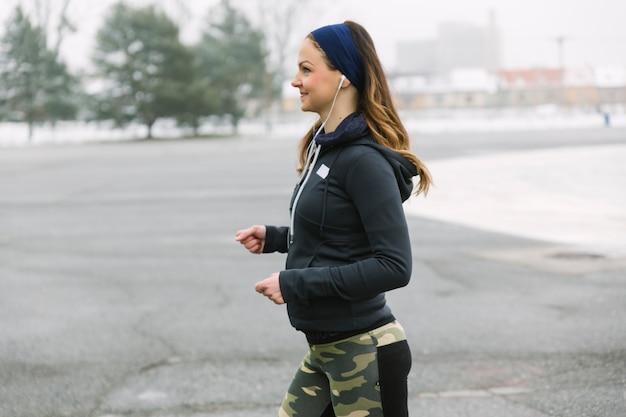 Seitenansicht des weiblichen athleten laufend auf straße Kostenlose Fotos