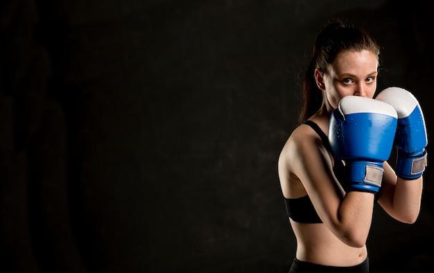 Seitenansicht des weiblichen boxers, der mit kopienraum aufwirft Kostenlose Fotos