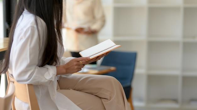 Seitenansicht des weiblichen universitätsstudenten, der ein buch liest, während auf holzstuhl sitzend Premium Fotos