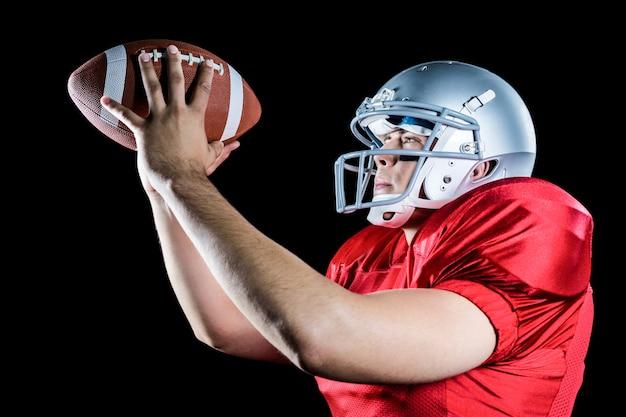 Seitenansicht des werfenden balls des spielers des amerikanischen fußballs Premium Fotos