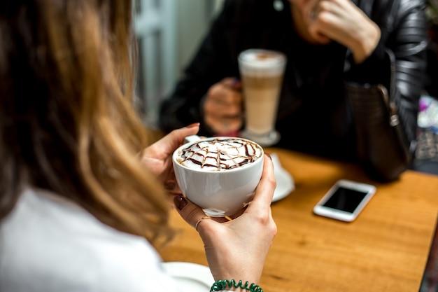 Seitenansicht ein mädchen trinkt cappuccino Kostenlose Fotos