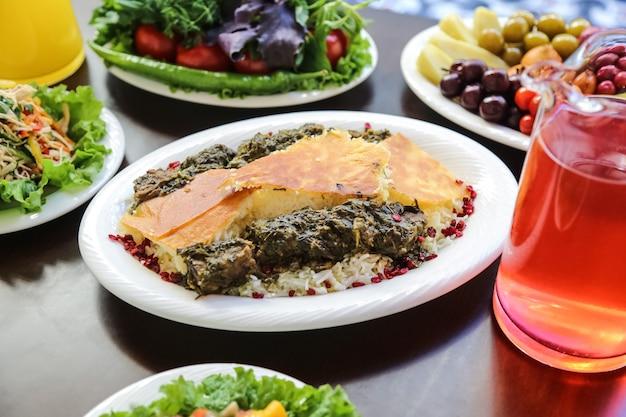 Seitenansicht ein traditionelles aserbaidschanisches gericht syabzi pilaw fleisch mit kräutern und gekochtem reis auf einem teller mit kompott Kostenlose Fotos