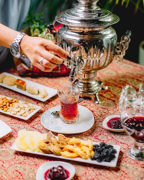 Seitenansicht eine frau gießt tee aus einer samowar-teekanne in ein glas armuda auf einer untertasse Kostenlose Fotos