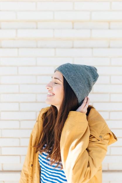 Seitenansicht einer glücklichen frau mit ihren augen schloss tragende strickmütze Kostenlose Fotos