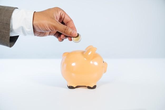 Seitenansicht einer hand, die eine münze in ein keramisches sparschwein mit einem weißen hintergrund und sehr gutem licht setzt Premium Fotos