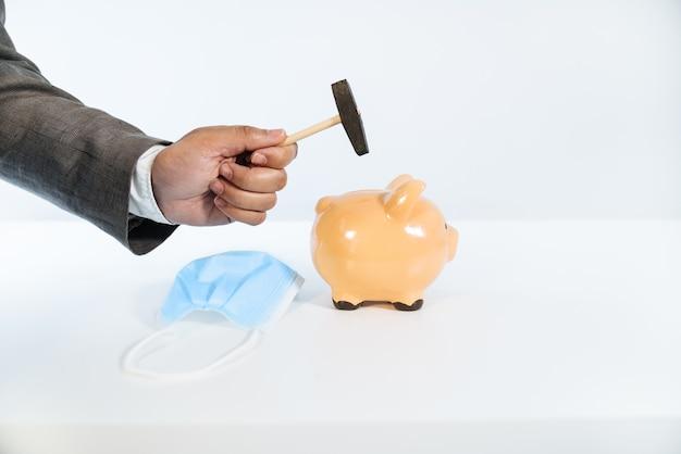 Seitenansicht einer hand mit einem hammer, der ein keramisches sparschwein mit einem weißen hintergrund und sehr gutem licht und einer gesichtsmaske aufgrund der covid19 coronavirus-pandemie bricht Premium Fotos