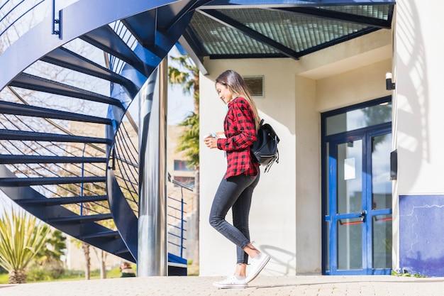 Seitenansicht einer jugendstudentin, die vor hochschulgebäude geht Kostenlose Fotos