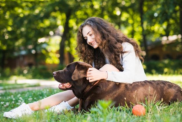 Seitenansicht einer lächelnden jungen frau, die ihren hund im garten streicht Kostenlose Fotos
