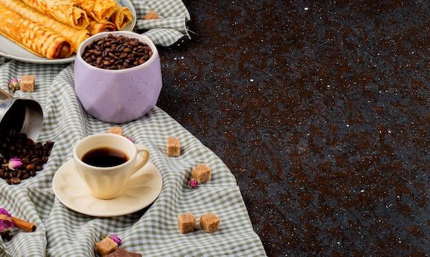 Seitenansicht einer tasse kaffee und brauner zuckerwürfel schokolade und kaffeebohnen verstreut auf der karierten tischdecke mit kopierraum Kostenlose Fotos
