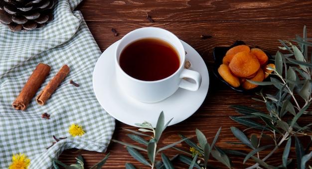 Seitenansicht einer tasse tee mit getrockneten aprikosen und zimtstangen auf holz Kostenlose Fotos