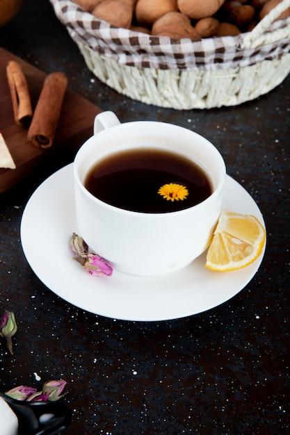 Seitenansicht einer tasse tee mit zitronenscheibe und zimtstange und einem korb mit walnüssen auf schwarz Kostenlose Fotos
