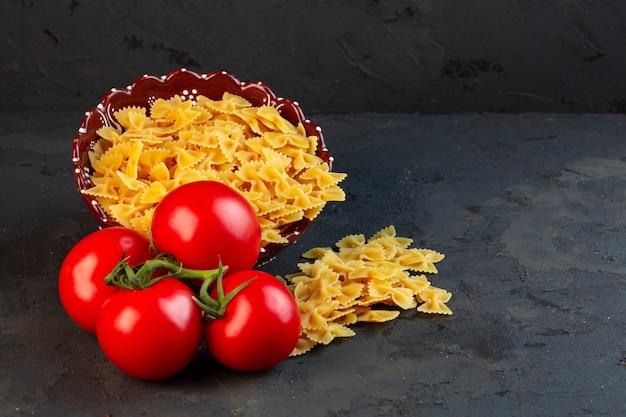 Seitenansicht eines bündels frischer tomaten mit rohen nudelfarfalle, die auf schwarz verstreut sind Kostenlose Fotos