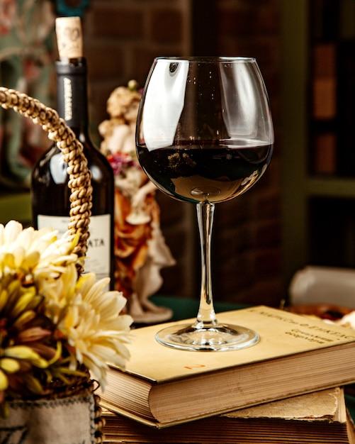 Seitenansicht eines glases rotwein auf buch Kostenlose Fotos