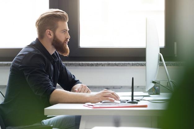 Seitenansicht eines jungen bärtigen mannes, der an seinem schreibtisch sitzt Kostenlose Fotos