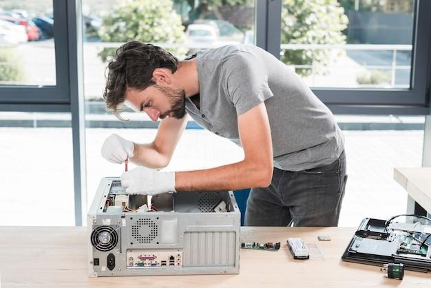 Seitenansicht eines jungen männlichen technikers, der computer in der werkstatt repariert Kostenlose Fotos