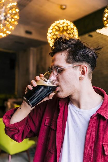 Seitenansicht eines jungen mannes, der das bier in der kneipe trinkt Kostenlose Fotos