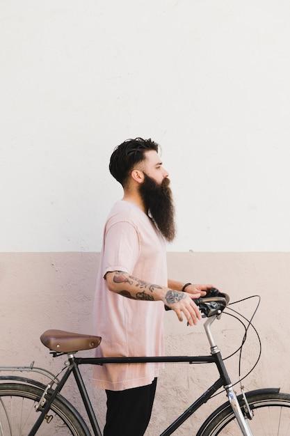 Seitenansicht eines jungen mannes, der mit seinem fahrrad gegen wand steht Kostenlose Fotos