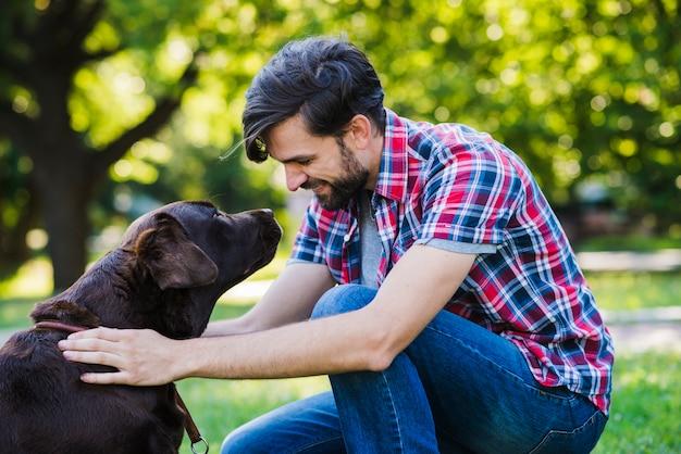 Seitenansicht eines jungen mannes, der seinen hund betrachtet Kostenlose Fotos