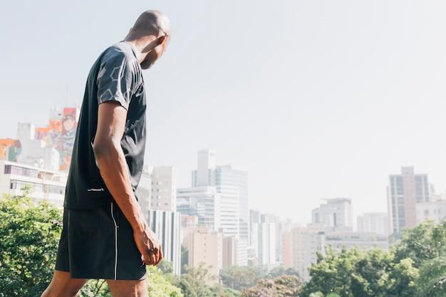 Seitenansicht eines jungen mannes des athleten, der stadtskyline betrachtet Kostenlose Fotos