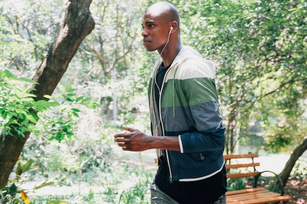 Seitenansicht eines jungen mannes mit kopfhörer in seinem ohr, das in den park läuft Kostenlose Fotos