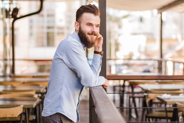 Seitenansicht eines lächelnden jungen mannes, der im restaurant steht Kostenlose Fotos