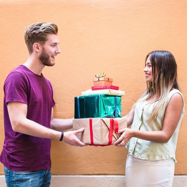 Seitenansicht eines lächelnden jungen paarholdingstapels geschenke Kostenlose Fotos