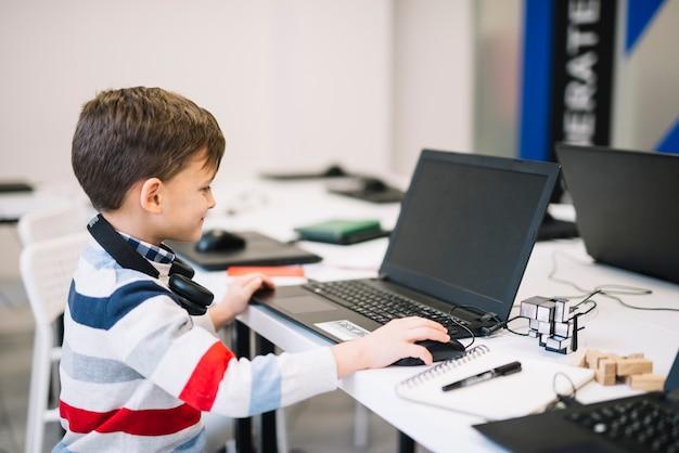 Seitenansicht eines lächelnden kleinen jungen, der laptop und maus im klassenzimmer verwendet Kostenlose Fotos