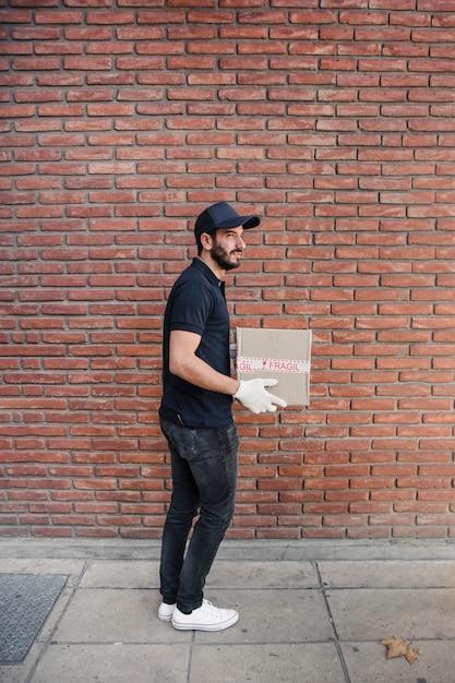 Seitenansicht eines lieferers mit paket vor brickwall Kostenlose Fotos