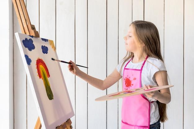 Seitenansicht eines mädchens, das in der hand die hölzerne palette malt auf dem gestell mit malerpinsel hält Kostenlose Fotos