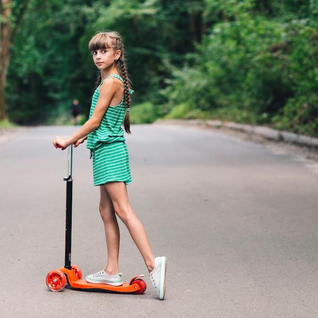 Seitenansicht eines mädchens, das über dem roller auf straße steht Kostenlose Fotos