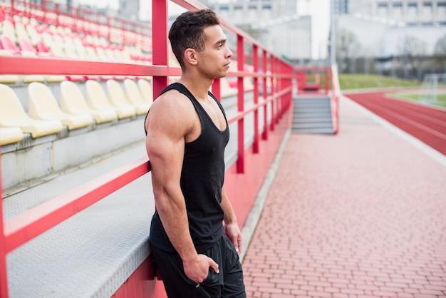 Seitenansicht eines männlichen athleten, der den nahen zuschauertribünen weg schaut steht Kostenlose Fotos