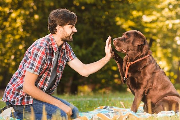 Seitenansicht eines mannes, der seinem hund im garten hoch fünf gibt Kostenlose Fotos