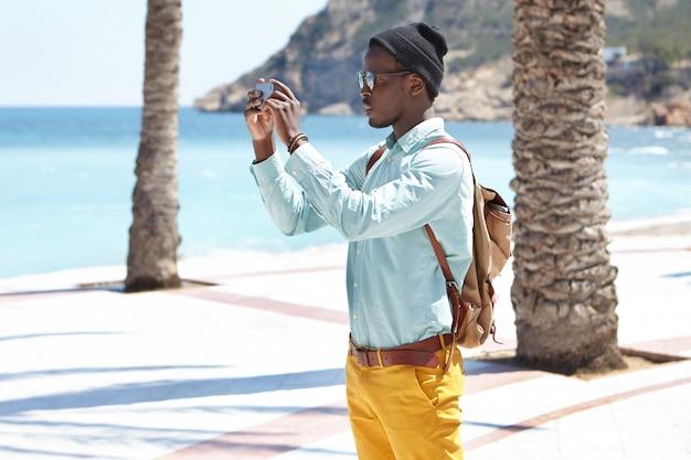 Seitenansicht eines modischen jungen schwarzen reisenden in den ferien, der das smartphone mit beiden händen hält, während er bilder macht oder ein video von schönheit um ihn herum aufzeichnet, um sie auf seinen social-media-konten zu veröffentlichen Kostenlose Fotos
