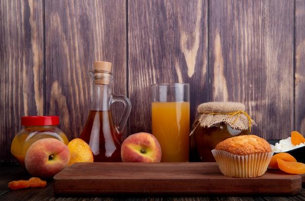 Seitenansicht eines muffins auf holzbrett und frischen reifen pfirsichen mit einem glas pfirsichsaft und pfirsichmarmelade in einem glas auf rustikalem hintergrund Kostenlose Fotos